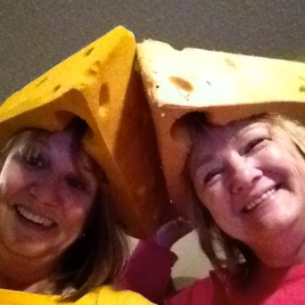 Packers fans Kathy Olson and Neva Potter sport their cheeseheads Sunday and cheer the Green Bay Packers from home while their husbands watched the game at Lambeau Field.